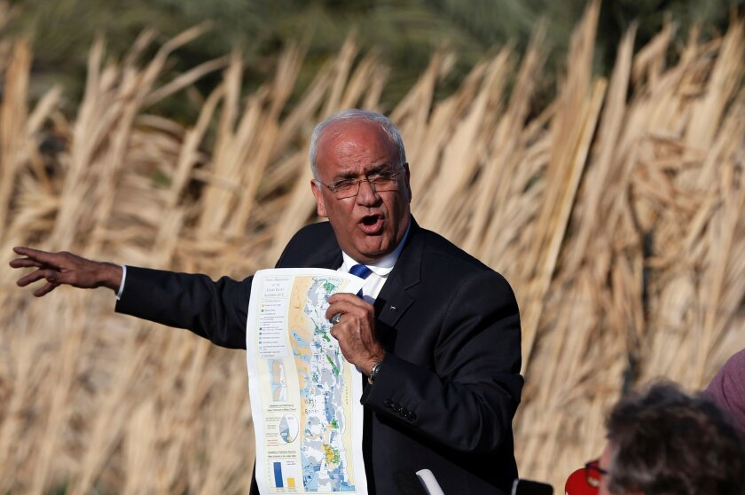 Saeb Erekat shows a map as he addresses journalists in the West Bank city of Jericho.