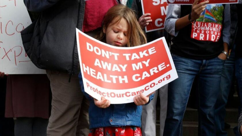 A girl stands holding a sign alongside supporters of the Affordable Care Act who are also opponents of Colorado's GOP-led plan to undo Colorado's state-run insurance exchange at a rally on the state Capitol steps in Denver, Tuesday, Jan. 31, 2017.