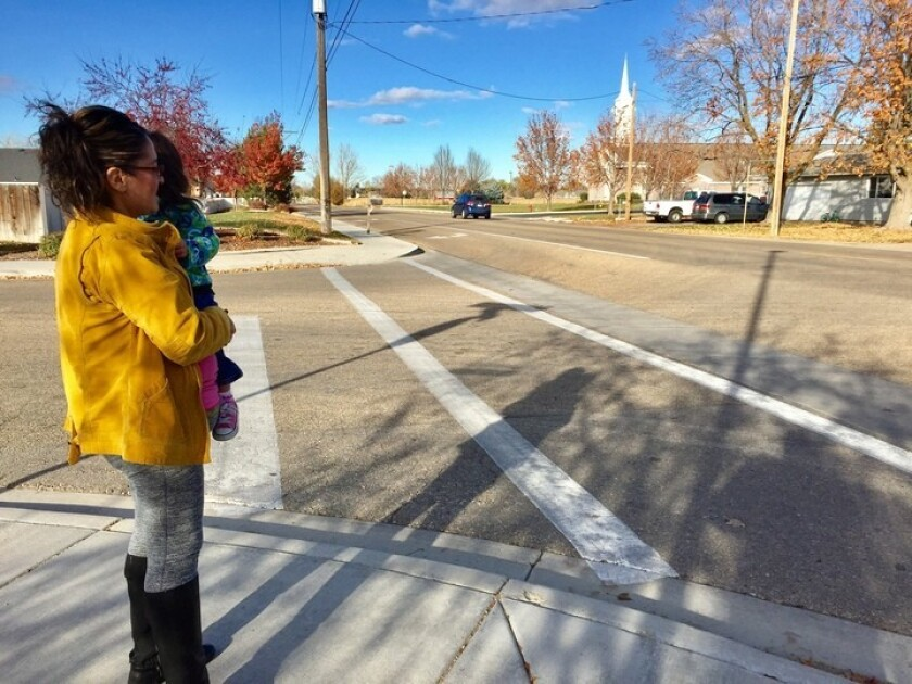 Janeth Calderon, holding daughter Sarnay, 2, waits for her children's school bus in Caldwell, Idaho.