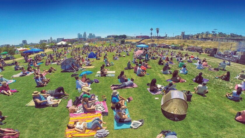 People participate in a mass meditation at the Los Angeles State Historic Park.