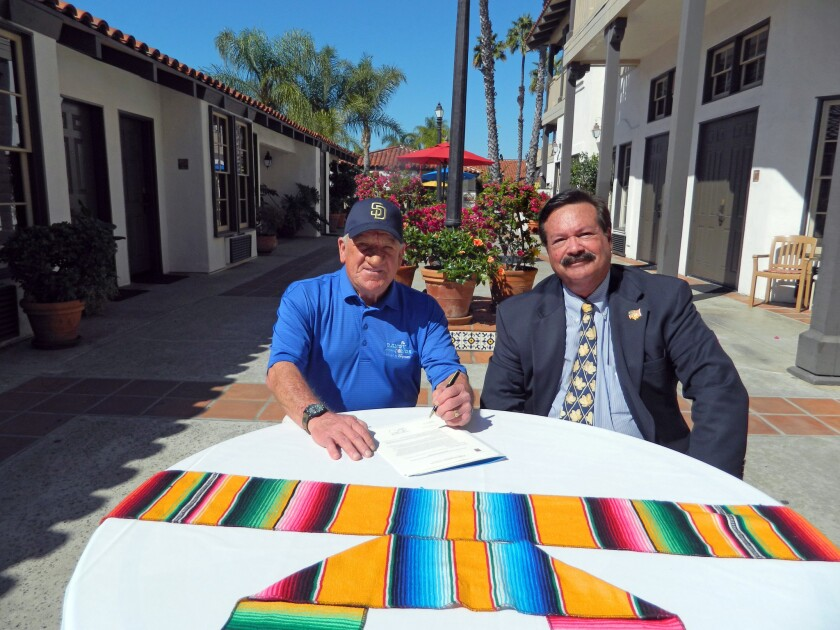 Randy Jones, San Diego Padres and Breitbard Hall of Fame member and 1976 Cy Young Award winner, and Fred Grand, president, Pacific Hospitality Group, Inc.,sign an agreement for a major joint effort between the Randy Jones Golf Invitational and Pacific Hospitality Group.