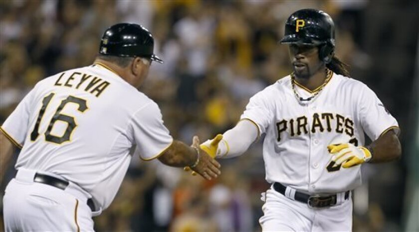 Pittsburgh Pirates' Andrew McCutchen (22) is greeted by third base coach Nick Leyva after hitting a home run in the fourth inning of a baseball game against the Miami Marlins,Wednesday, Aug. 7, 2013, in Pittsburgh. (AP Photo/Keith Srakocic)