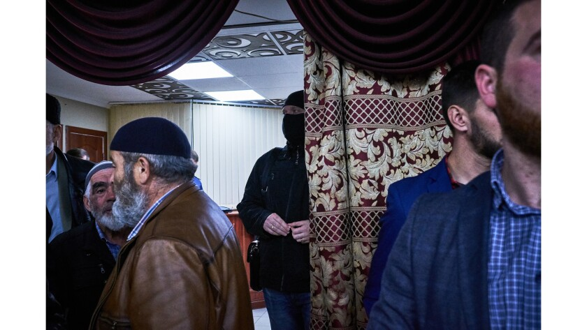A masked member of Russia's Office of Counterterrorism stands in the entrance of a banquet hall wher