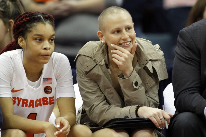 FILE - In this Nov. 24, 2019, file photo, Syracuse's Tiana Mangakahia, right, sits on the Syracuse bench during an NCAA college basketball game against Oregon in Syracuse, N.Y. Mangakahia returned to the basketball court, Sunday, Nov. 29, 2020, after not playing competitively for 615 days while battling breast cancer. (AP Photo/Nick Lisi, File)