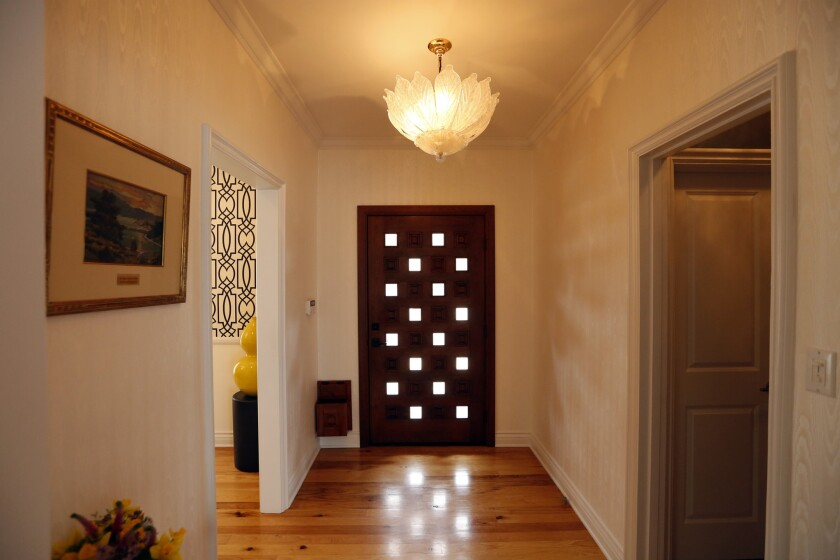 The entryway includes another Murano glass lighting fixture as well as a wood door with glass placed
