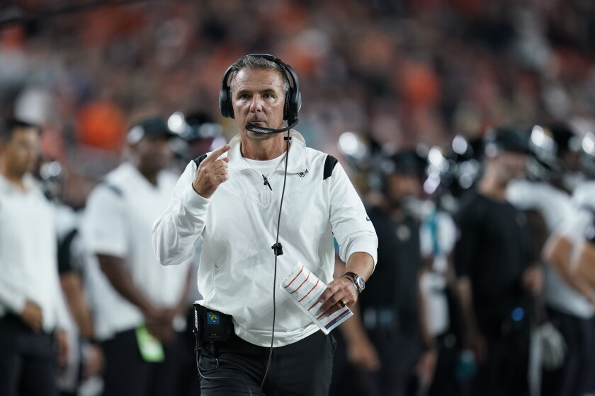 Jacksonville Jaguars head coach Urban Meyer walks with an official during the first half of an NFL football game against the Cincinnati Bengals, Thursday, Sept. 30, 2021, in Cincinnati. (AP Photo/Michael Conroy)