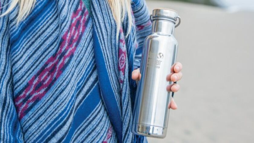 Woman on a beach holding a Klean Kanteen Insulated Reflect bottle. Credit: Klean Kanteen
