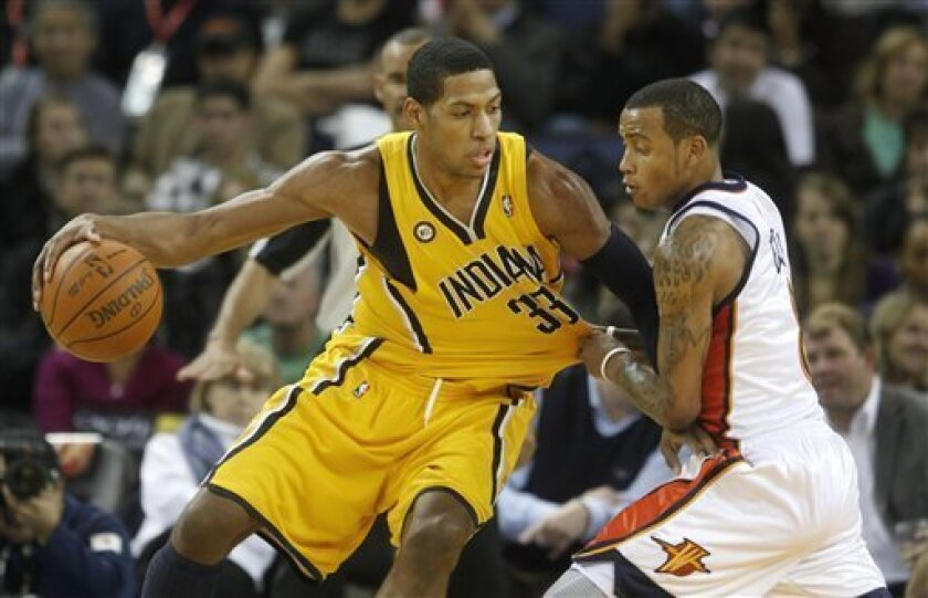 Indiana Pacers forward Danny Granger (33) is fouled by Golden State Warriors guard Monta Ellis (8) in the second quarter of an NBA basketball game in Oakland, Calif., Monday, Nov. 30, 2009. (AP Photo/Jeff Chiu)