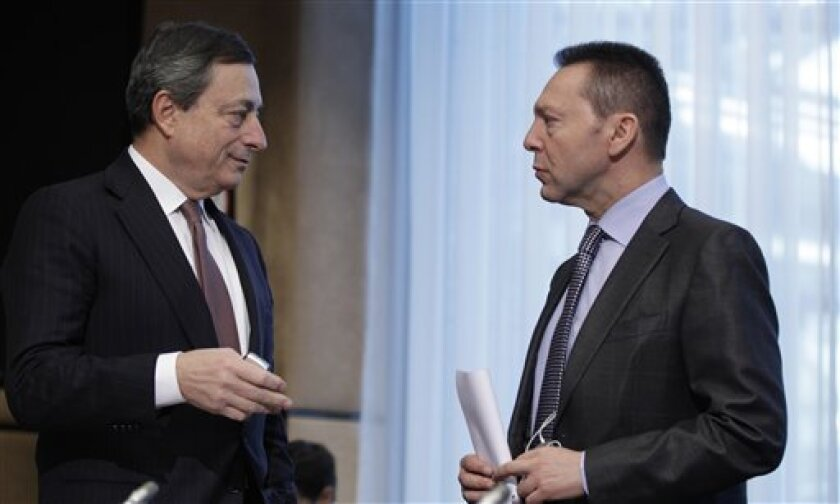 European Central Bank President Mario Draghi, left, speaks with Greek Finance Minister Yannis Stournaras during a meeting of the Macroeconomic Dialogue Group prior to a meeting of the eurogroup ministers in Brussels on Monday, March 4, 2013. The eurogroup finance ministers are set to discuss detail