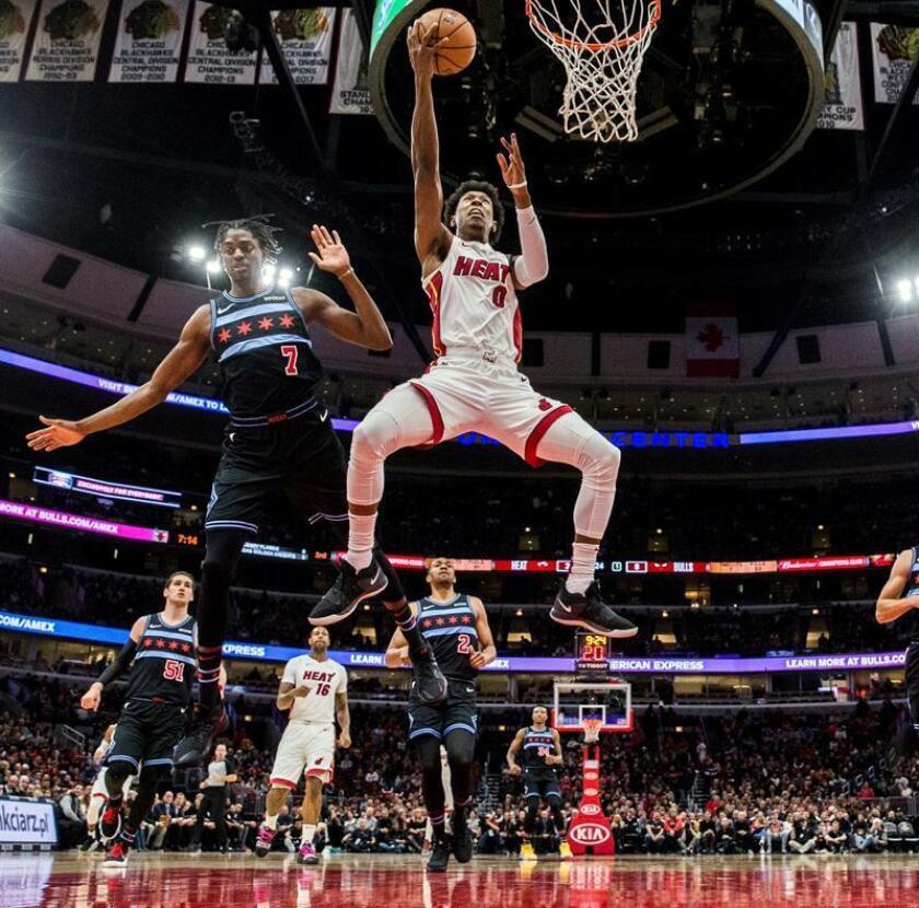 El alero de los Miami Heat Josh Richardson (d) entra a canasta ante la oposición del jugador de os Chicago Bulls Justin Holiday (i), durante el partido disputado hoy en Chicago. EFE
