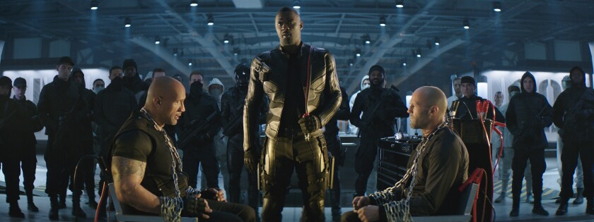"""Dwayne Johnson, left, and Jason Statham sit facing each other, with Idris Elba standing near, in """"Fast & Furious Presents: Hobbs & Shaw."""""""