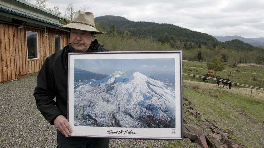 Mark Smith, owner of the Eco Park Resort, holds a photo of Mt. St. Helens on his property near the volcano. Smith's family owned and operated the Spirit Lake Lodge until it was destroyed when Mt. St. Helens erupted on May 18, 1980.