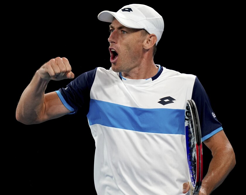 Australia's John Millman celebrates a point win against Switzerland's Roger Federer during their third round match at the Australian Open tennis championship in Melbourne, Australia, Friday, Jan. 24, 2020. (AP Photo/Lee Jin-man)