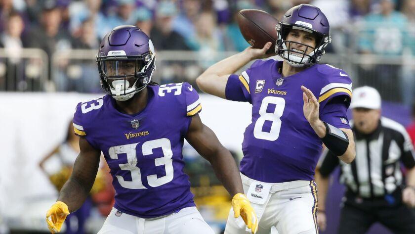 Minnesota Vikings quarterback Kirk Cousins (8) throws a pass as teammate Dalvin Cook (33) blocks dur