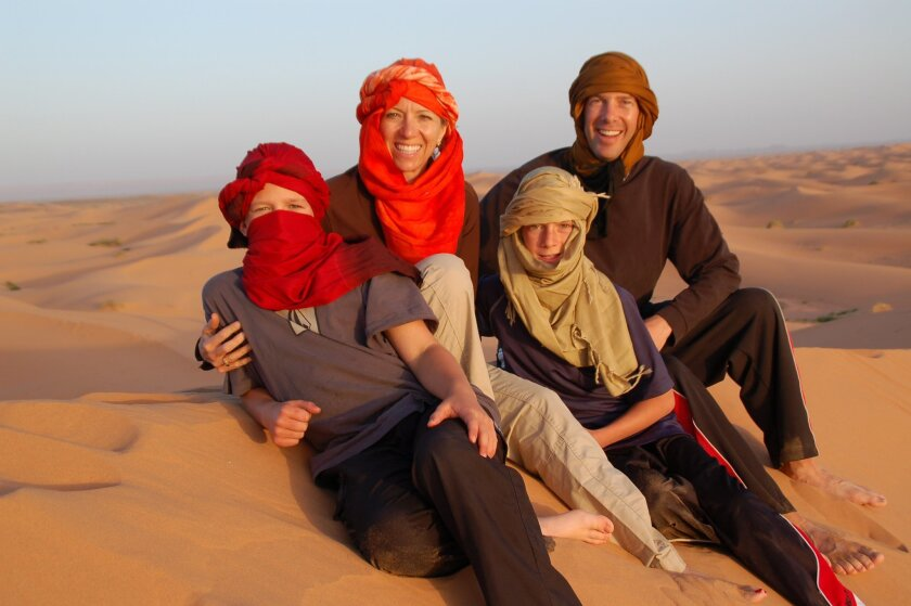 The Piegza family sits on 1,000-foot-tall sand dunes in Merzouga in Morocco, a Classic Journeys destination.