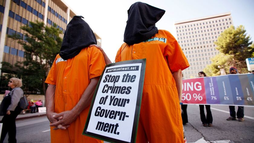 "Demonstrators wearing orange jumpsuits and hoods protest the ""shame and torture done in the name of the United States"" during an Interfaith Communities United for Justice and Peace rally in downtown Los Angeles in 2011."