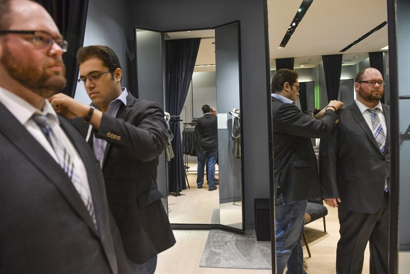 Kiavash Asghari, center, measures customer Bobby Bartlett for a new suit at Indochino in McLean, Va.