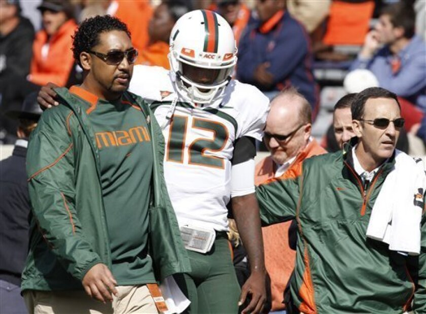Miami quarterback Jacory Harris (12) is helped from the field afte getting injured during the second quarter of an NCAA college football game against Virginia at Scott Stadium in Charlottesville, Va., Saturday, Oct. 30, 2010. (AP Photo/Steve Helber)