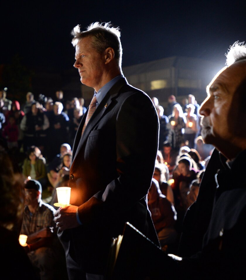 Gov. Charlie Baker attends a candlelight vigil for Bella Bond on Deer Island in Boston on Monday, Sept. 21, 2015. Bella Bond, 2, was known as Baby Doe until she was identified almost three months after her remains washed up inside a trash bag on the Boston Harbor beach. Michael McCarthy, 25, is charged with killing 2-year-old Bella. The girl's mother, Rachelle Bond, 40, is charged with being an accessory after her daughter's killing. Both are charged with unlawful disposal of human remains. (Christopher Evans/The Boston Herald via AP) BOSTON GLOBE OUT; METRO BOSTON OUT; MAGS OUT; ONLINE OUT; MANDATORY CREDIT