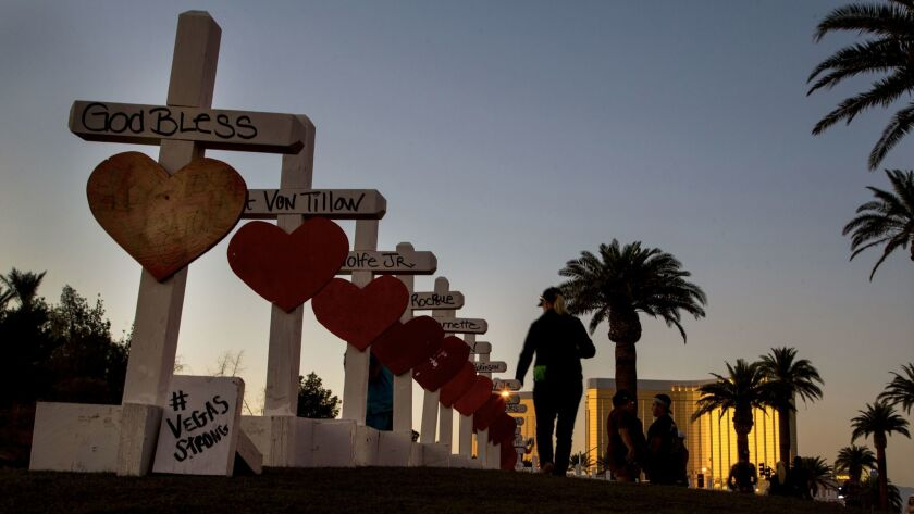 A woman walks beside 58 white crosses for the victims of the Oct. 1 mass shooting on the Las Vegas Strip.