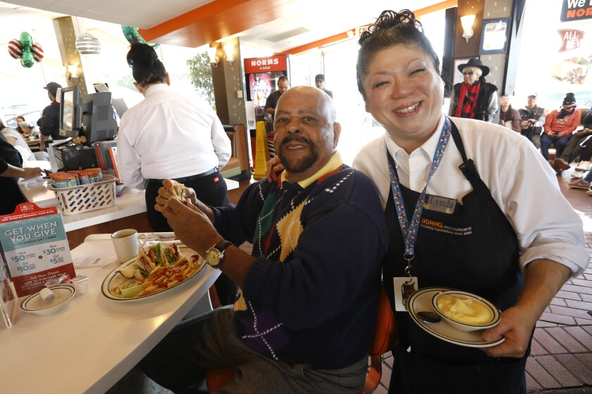 Amid the chaos of a post-Christmas December morning at Norms, customer Paul Welch and waitress Lynda Sato find a moment to share a smile for the camera.