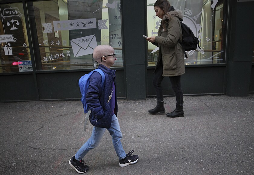 In this Feb. 12, 2019 photo, Meghan Waldron walks down the street in Boston. Waldron is a freshman at Emerson College with progeria, one of the world's rarest diseases. The first treatment has been approved for progeria, Friday, Nov. 20, 2020. The U.S. Food and Drug Administration on Friday approved Zokinvy which was shown in testing to extend patients' lives by 2 ½ years on average. (Suzanne Kreiter/The Boston Globe via AP)