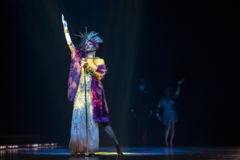 A woman in old Hollywood glam stands on a stage in multicolored light and raises her hand to the sky