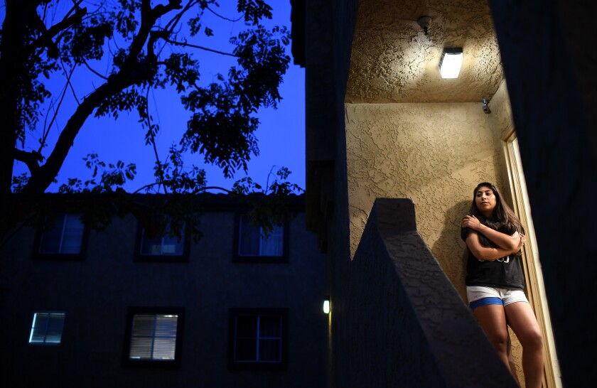 Melanie Santos, outside her Pico Rivera apartment, has lost work as a substitute teacher.