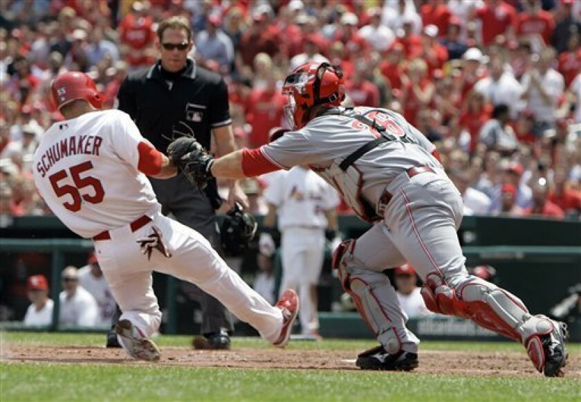 St. Louis Cardinals' Skip Schumaker, left, scores on a single by teammate Aaron Miles as Cincinnati Reds catcher David Ross, right, attempts the tag during the third inning of a baseball game Wednesday, April 30, 2008, in St. Louis. Schumaker was called safe by home plate umpire Jim Wolf, center. (AP Photo/Jeff Roberson)