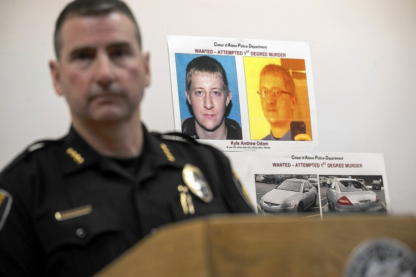 Coeur d'Alene Police Chief Lee White at a news conference with photos of shooting suspect Kyle Andrew Odom before his capture.