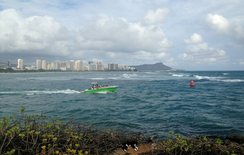 A boat maneuvers out to sea near Point Panic in Honolulu, Monday, Aug. 24, 2015. Tropical Depression Kilo moved farther away from the main Hawaiian Islands on Monday after moisture associated with the system dumped heavy rain on the state. Heavy rain caused wastewater to spew from manholes near the popular tourist destination of Waikiki, said Markus Owens, a spokesman for the state Department of Environmental Services. (AP Photo/Cathy Bussewitz)