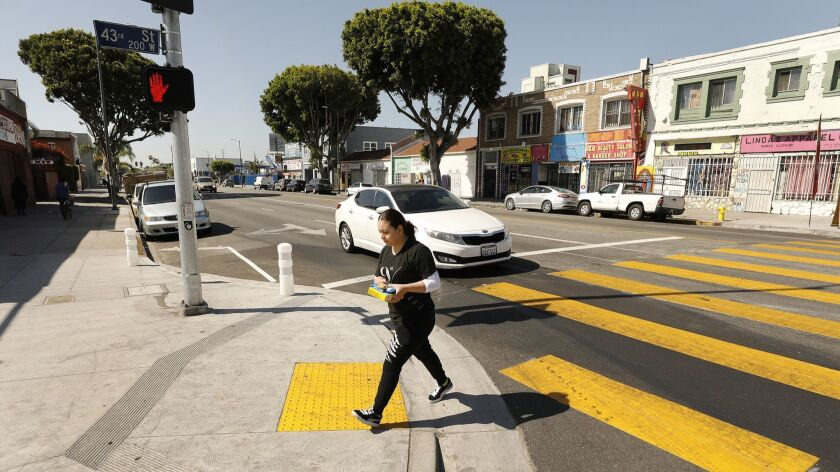LOS ANGELES, CA - APRIL 17, 2019 - Pedestrians use new crosswalks at 43rd and Broadway which include