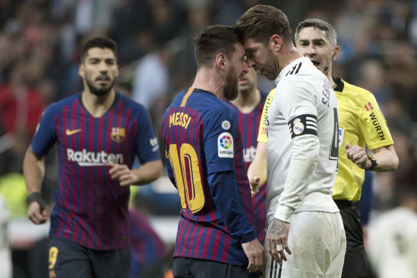 Barcelona's Argentinian forward Lionel Messi (2L) argues with Real Madrid's Spanish defender Sergio Ramos during the Spanish league football match between Real Madrid CF and FC Barcelona at the Santiago Bernabeu stadium in Madrid on March 2, 2019.