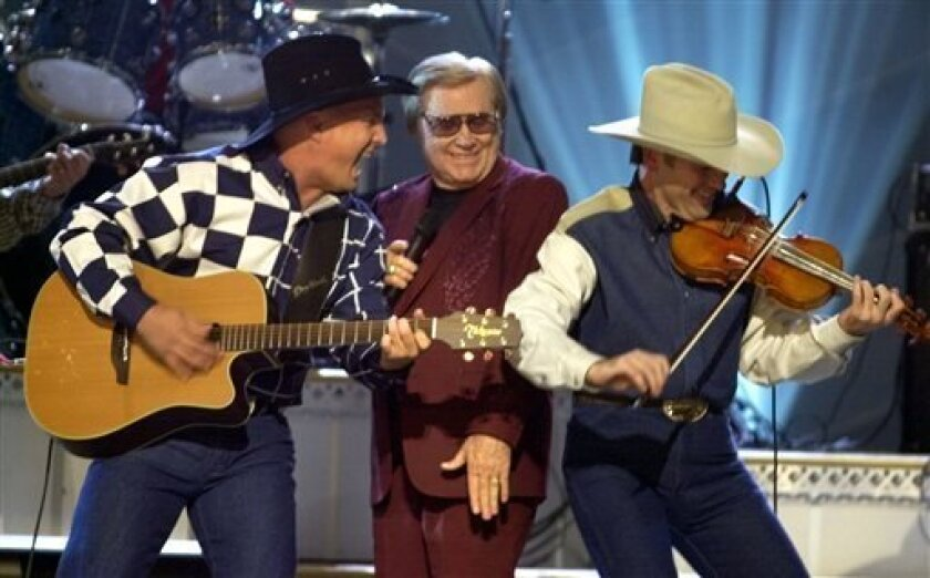 """FILE - In this Nov. 7, 2001 file photo, Garth Brooks, left, and George Jones, center, perform their duet """"Beer Run"""" at the Country Music Association Awards show in Nashville, Tenn. The fiddle player at right is unidentified.   Jones died Friday, April 26, 2013 at Vanderbilt University Medical Cente"""