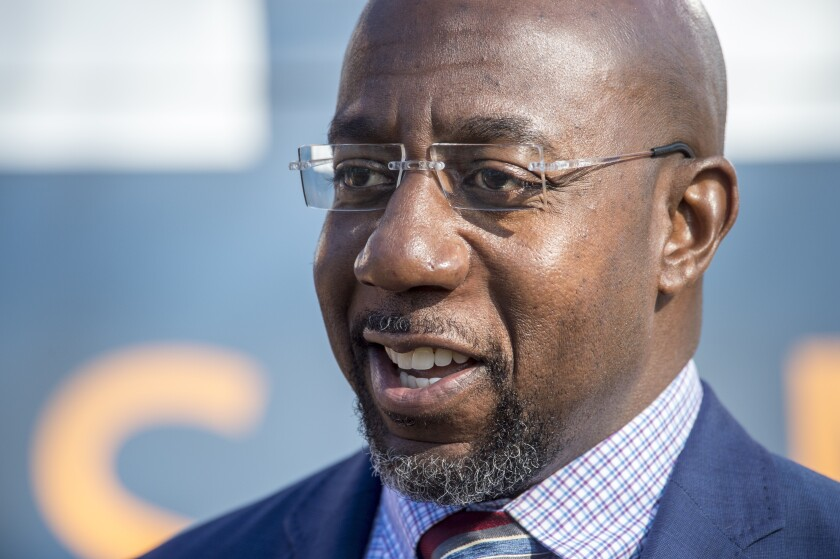 Georgia Democratic senate candidate Raphael Warnock talks to reporters following a campaign rally in Augusta, Ga., Monday, Jan. 4, 2021. Democrats Jon Ossoff and Warnock are challenging incumbent Republican Senators David Perdue and Kelly Loeffler in a runoff election on Jan. 5. (Michael Holahan/The Augusta Chronicle via AP)