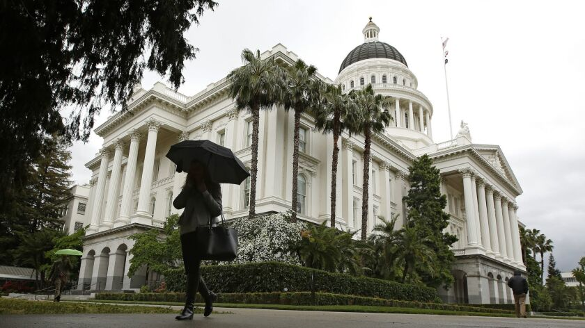FILE - In this May 16, 2019, file photo a woman uses an umbrella as it rains at the Capitol in Sacra