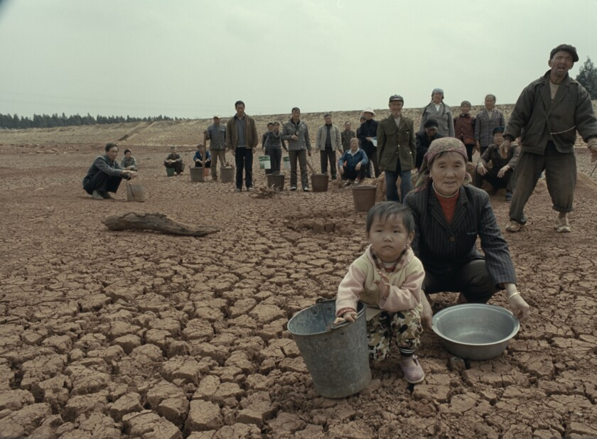 "Families on a dry river or lake bed in Wang Xiaoshuai's documentary ""Chinese Portrait."""