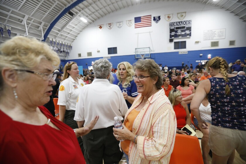 Trona residents trade earthquake stories before a community meeting Trona High School on Wednesday.
