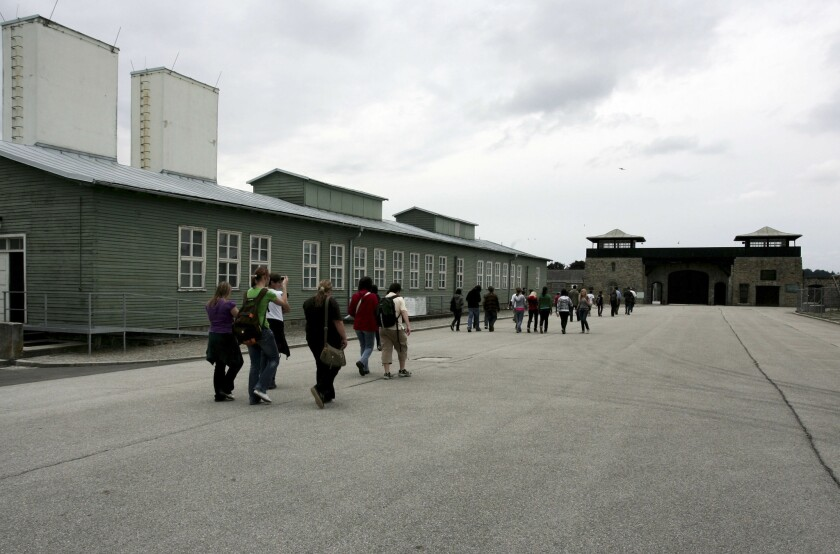 People arrive at Austria's Mauthausen concentration camp, where one alleged camp guard is charged with being an accessory to murder.