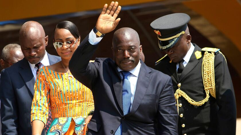 Congolese President Joseph Kabila waves as he and others celebrate independence day for the Democratic Republic of Congo in Kindu on June 30, 2016.