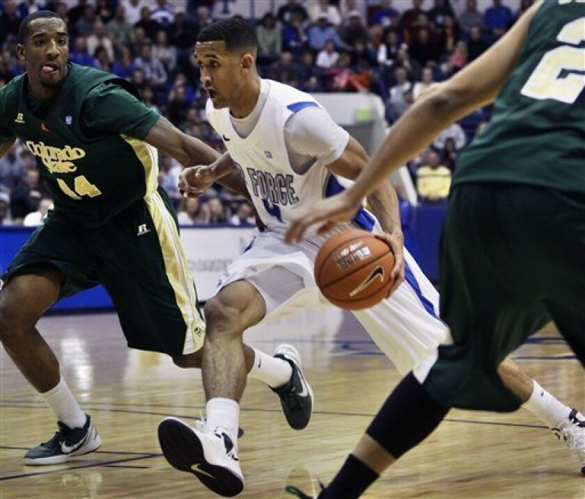 Air Force's Kamryn Williams, center, moves the ball downcourt while covered by Colorado State's Greg Smith, left, during the second half of an NCAA college basketball game in Air Force Academy, Colo., Saturday, Feb. 16, 2013. Colorado State won 89-86. (AP Photo/Brennan Linsley)