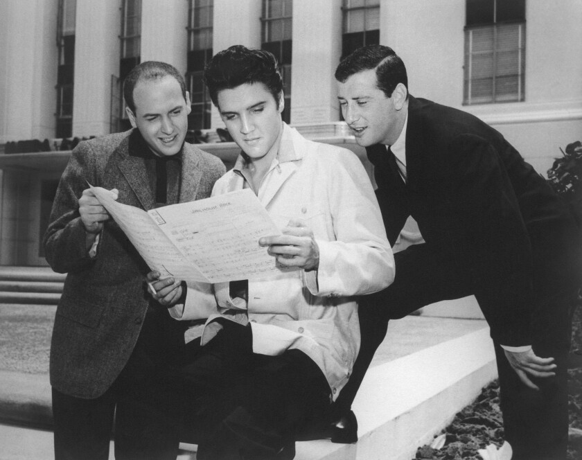 "Mike Stoller, Elvis Presley and Jerry Leiber looking over the sheet music for ""Jailhouse Rock."""