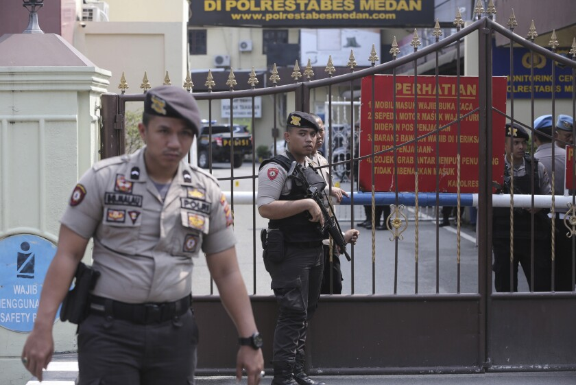 Police officers stand guard at the gate of the local police headquarters following a suicide bombing attack at the compound in Medan, North Sumatra, Indonesia, Wednesday, Nov. 13, 2019. Police say a suicide bomber has blown himself up at a busy police station in Indonesia's third-largest city, injuring a number of people. (AP Photo/Binsar Bakkara)