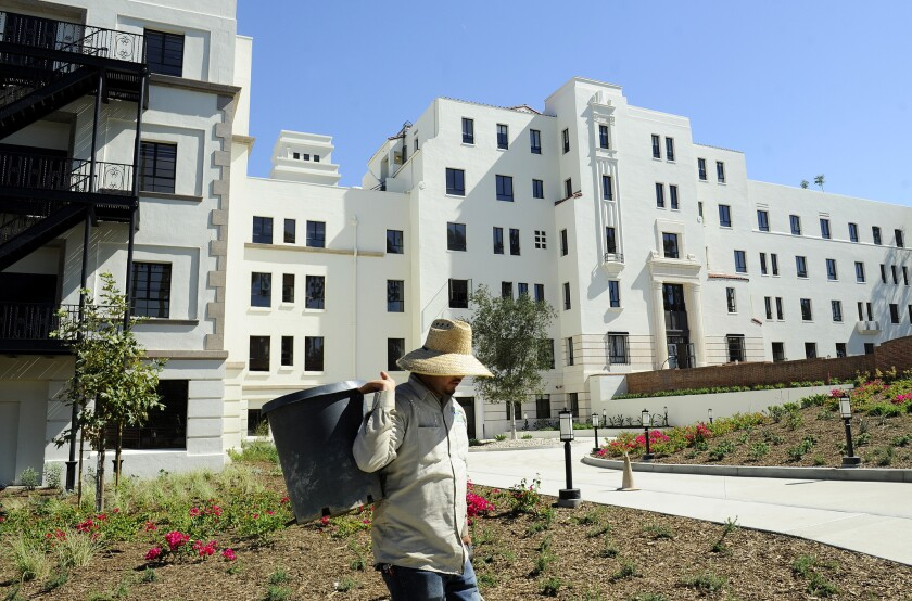 A gardener works in the yard at the former Linda Vista Hospital that is now affordable housing buildings.