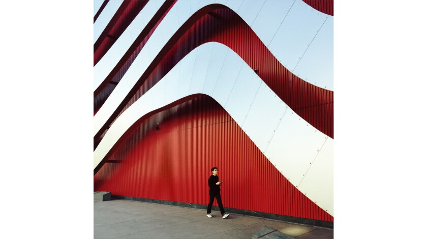 A pedestrian strolls by the Petersen Automotive Museum on Sunday.