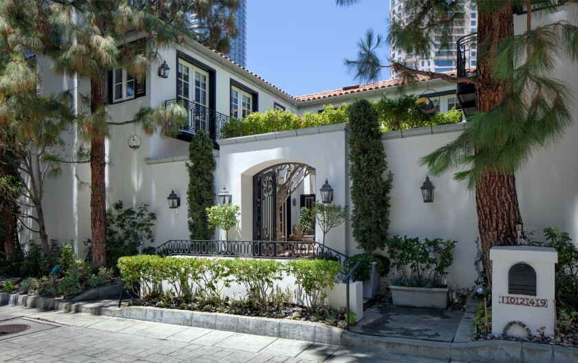 One of 36 homes in a guard-gated enclave, the two-story villa is navigated by an elevator and sweeping staircase.