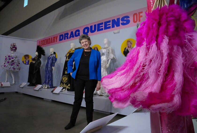 "Curator Lillian Faderman stands among the costumed mannequins featured in the ""Legendary Drag Queens of San Diego"" exhibit at the San Diego History Center."