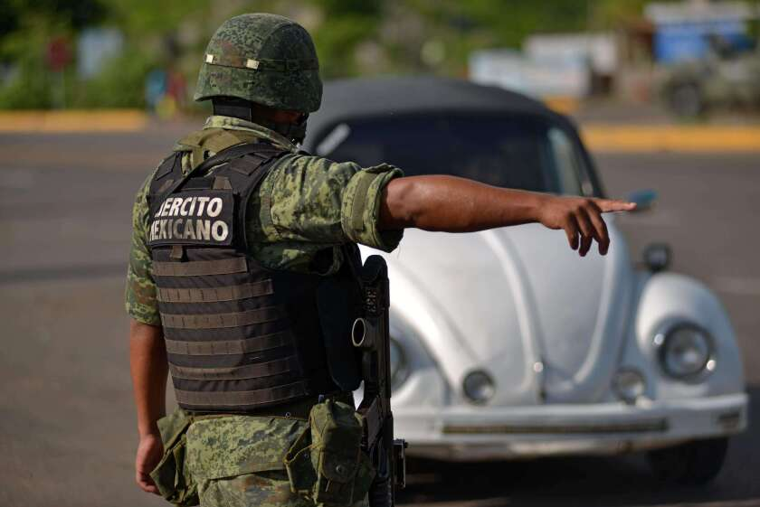 """A Mexican soldier stops a vehicle at a checkpoint Wednesday on the highway connecting Badiraguato, Joaquin """"El Chapo"""" Guzman's hometown, and Santiago de Los Caballeros, in Sinaloa state, Mexico."""