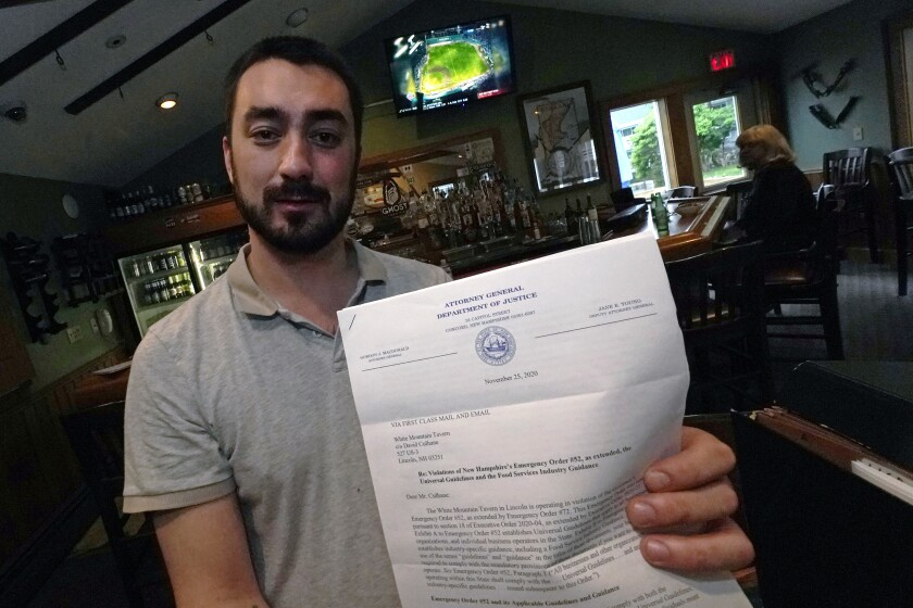 David Culhane, owner of the White Mountain Tavern, holds up a November 2020 letter from the N.H. Attorney General's office, notifying that his business was in violation, and also fined, after breaking an emergency order, Tuesday, July 13, 2021, in Lincoln, N.H. Culhane was fined $1,000 and later reached a settlement for holding a live music performance in November at which people crowded together, and for employees not wearing masks. A provision in the recently signed New Hampshire state budget will provide refunds to businesses that were fined for violating the governor's pandemic emergency orders. (AP Photo/Charles Krupa)
