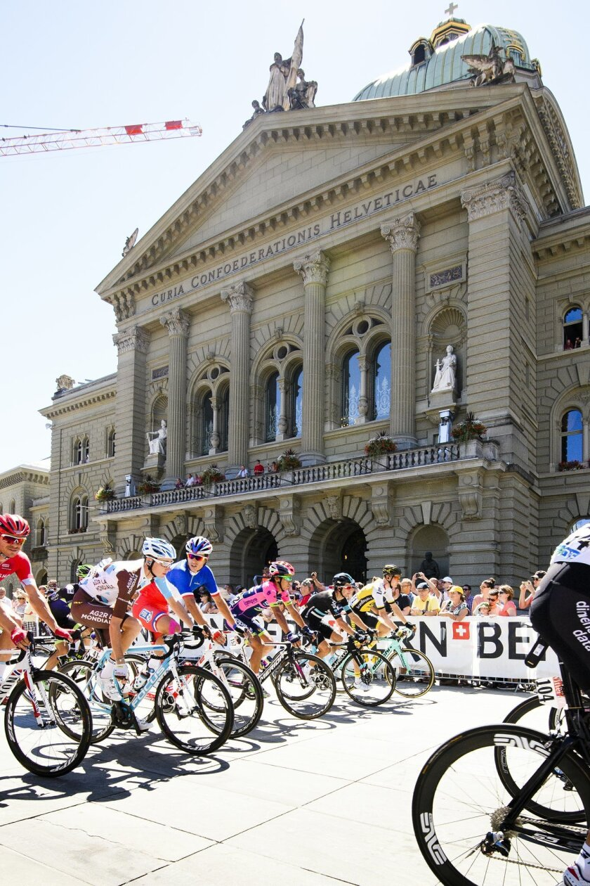 """The pack rides as it crosses the """"Bundesplatz""""  square with the Swiss federal parliament building in the background during the  seventeenth stage of the  Tour de France cycling race over 184km between Bern and Finhaut-Emosson in Bern, Wednesday, July 20, 2016. (Manuel Lopez/Keystone via AP)"""